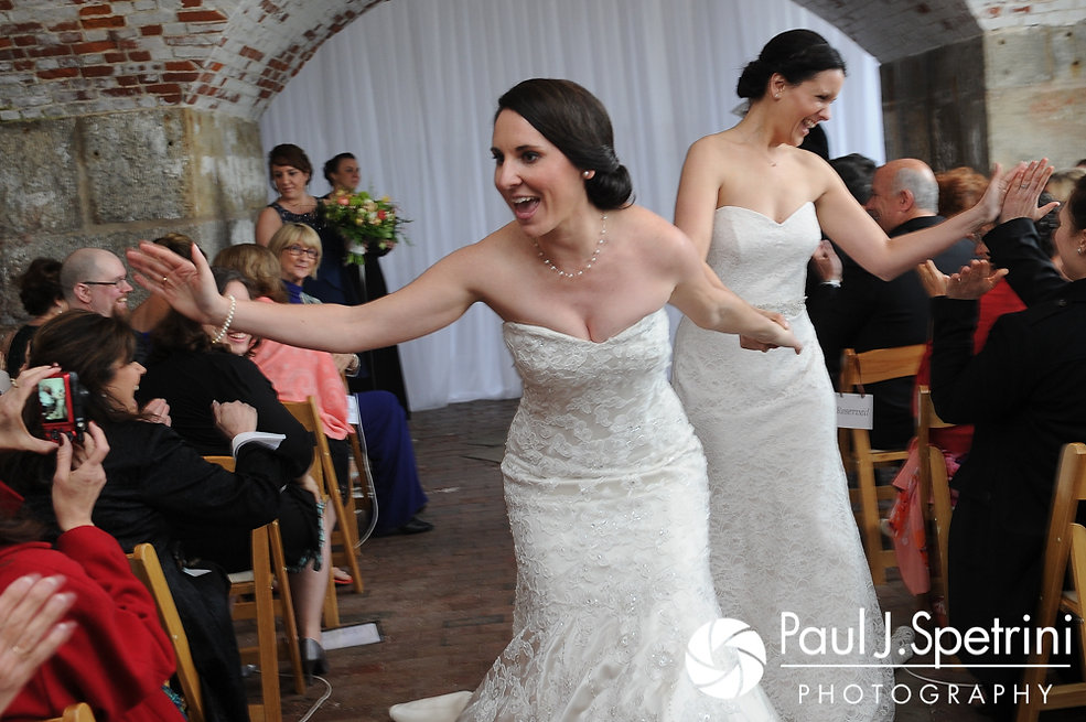 Caroline and Morgan high five guests following their April wedding ceremony at the Fort Adams Trust in Newport, Rhode Island.