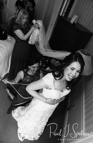 Sarah has help putting on her dress prior to her June 2018 wedding ceremony at the College of the Holy Cross in Worcester, Massachusetts.