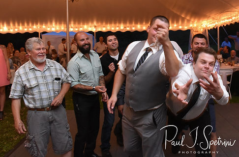 Wedding guests try to catch the garter during Karolyn & Ethan's August 2018 wedding reception at a private residence in Sterling, Connecticut.