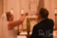 Courtney and Patrick light a candle during their September2018 wedding ceremony at St. Paul Church in Cranston, Rhode Island.