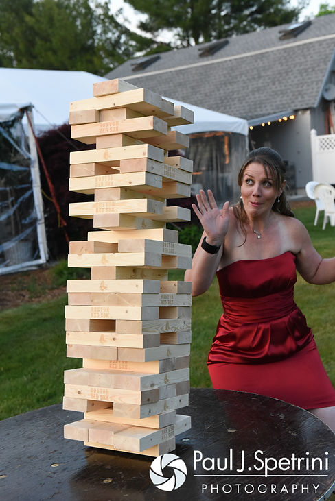 A bridesmaid plays giant Jenga at Latasha and Justin's May 2016 wedding at Country Gardens in Rehoboth, Massachusetts.