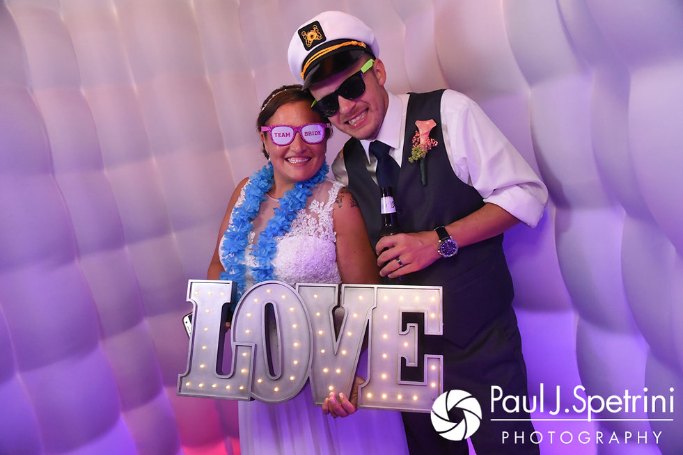 Scott and Toni smile for a photo in their photo booth during their August 2017 wedding reception at Crystal Lake Golf Club in Mapleville, Rhode Island.