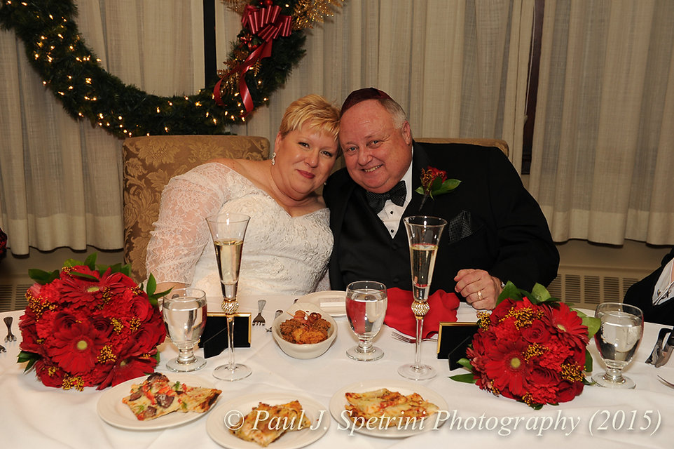 Cathy and Ron smile at the sweetheart table during their December 2015 Rhode Island wedding at Quidnessett Country Club in North Kingstown, RI.