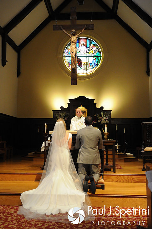 Amy and DJ kneel at the altar during their June 2016 wedding ceremony at St. Thomas More Church in Narragansett, Rhode Island.
