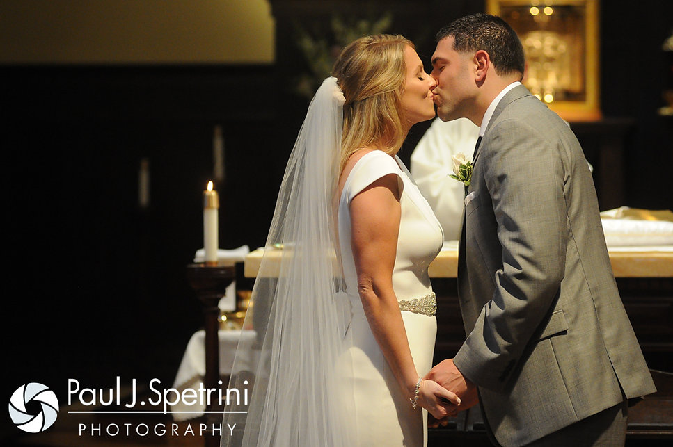 Amy & DJ share their first kiss during their June 2016 wedding ceremony at St. Thomas More Church in Narragansett, Rhode Island.