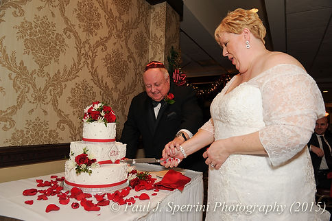 Cathy and Ron cut the wedding cake during their December 2015 Rhode Island wedding at Quidnessett Country Club in North Kingstown, RI.