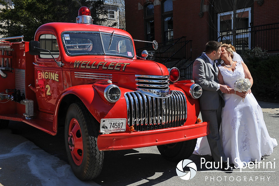 Angela and Shawn kiss in front of a fire truck parked outside the Kay Chapel in Newport, Rhode Island following their spring Rhode Island wedding.