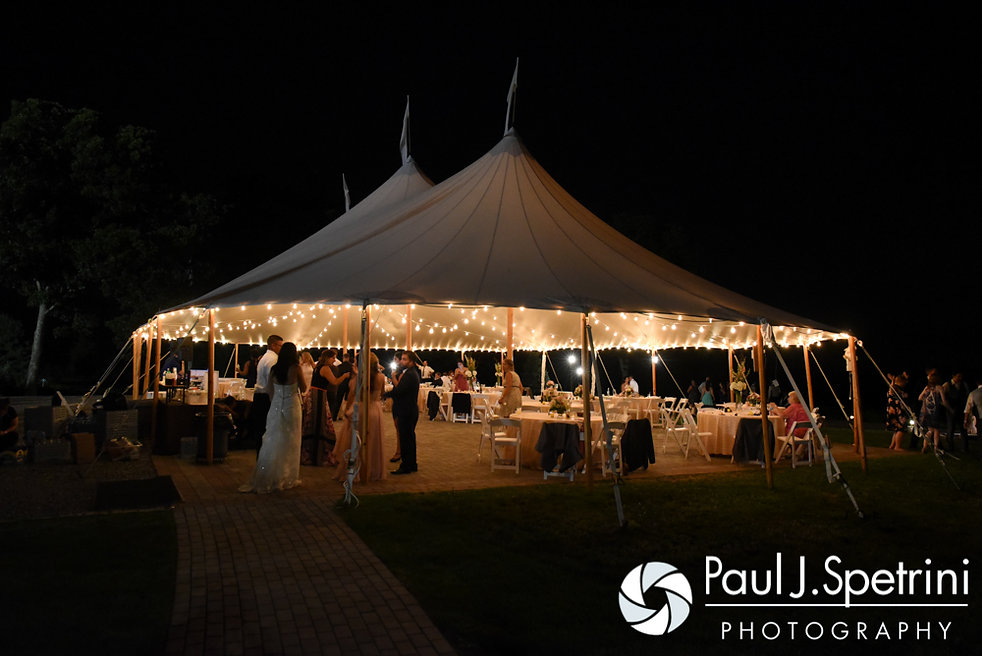 Guests enjoy the night under a tent at Lauryn and Justin's July 2016 wedding reception at the Overlook at Geer Tree Farm in Griswold, Connecticut.