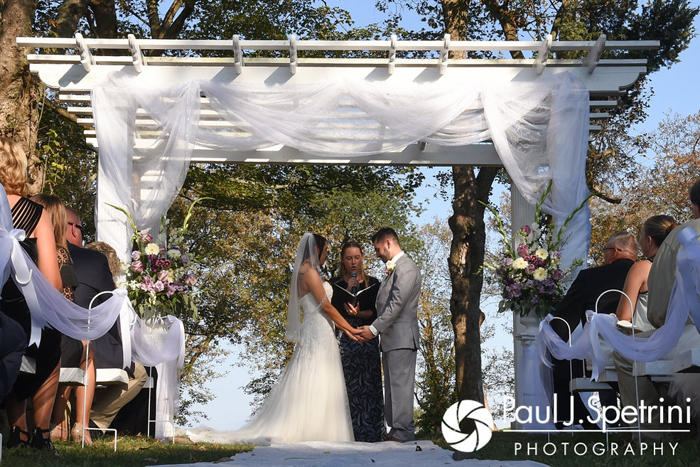 Stacey and John hold hands during their September 2017 wedding ceremony at Colt State Park in Bristol, Rhode Island.