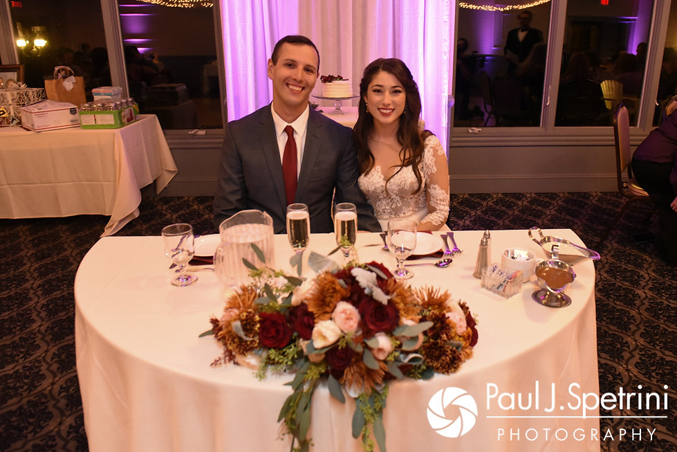 Keiran and Jessica smile at their sweetheart table during their October 2017 wedding reception at Crystal Lake Golf Club in Mapleville, Rhode Island.