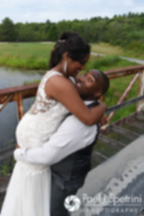 Kemi and Warren embrace for a formal photo following their August 2016 wedding reception at the Villa at Riddler Country Club in East Bridgewater, Massachusetts.
