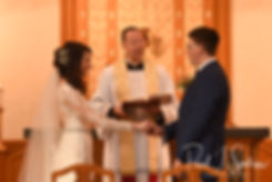 Stacey and Mack listen to their officiant during their December 2018 wedding ceremony at St. Teresa's Church in Attleboro, Massachusetts.