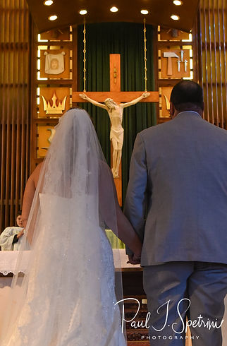 Sarah and Anthony hold hands during their October 2018 wedding ceremony at St. Augustine Catholic Church in Providence, Rhode island.