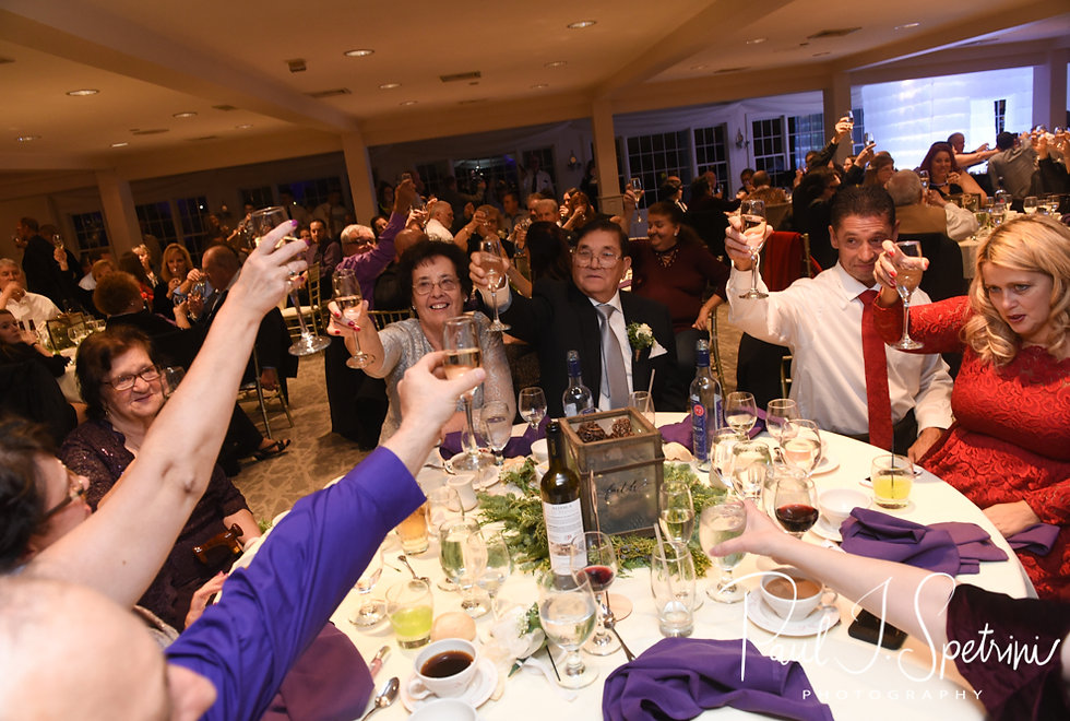 Guests raise their glasses after the best man gives a toast during Stacey & Mack's December 2018 wedding reception at Independence Harbor in Assonet, Massachusetts.