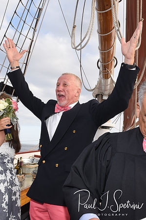 Mike raises his arms in celebration during his May 2018 wedding ceremony aboard the Schooner Aurora boat in the waters off Newport, Rhode Island.