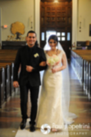 Maria and her brother walk down the aisle during her March 2016 Rhode Island wedding at the Church of St. John the Baptist in Pawtucket, Rhode Island.