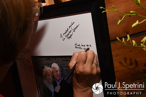 A guest signs a photo frame for Bob and Debbie during their June 2016 wedding reception at DeWolf Tavern in Bristol, Rhode Island.