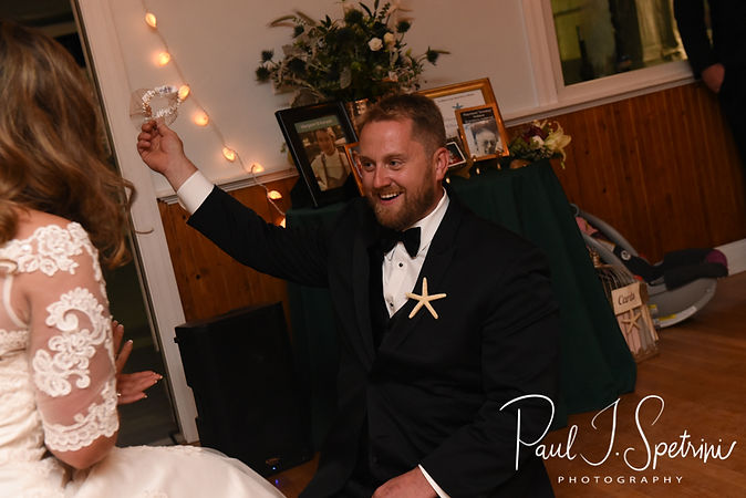 Brandon removes the garter during his November 2018 wedding reception at the North Beach Clubhouse in Narragansett, Rhode Island.