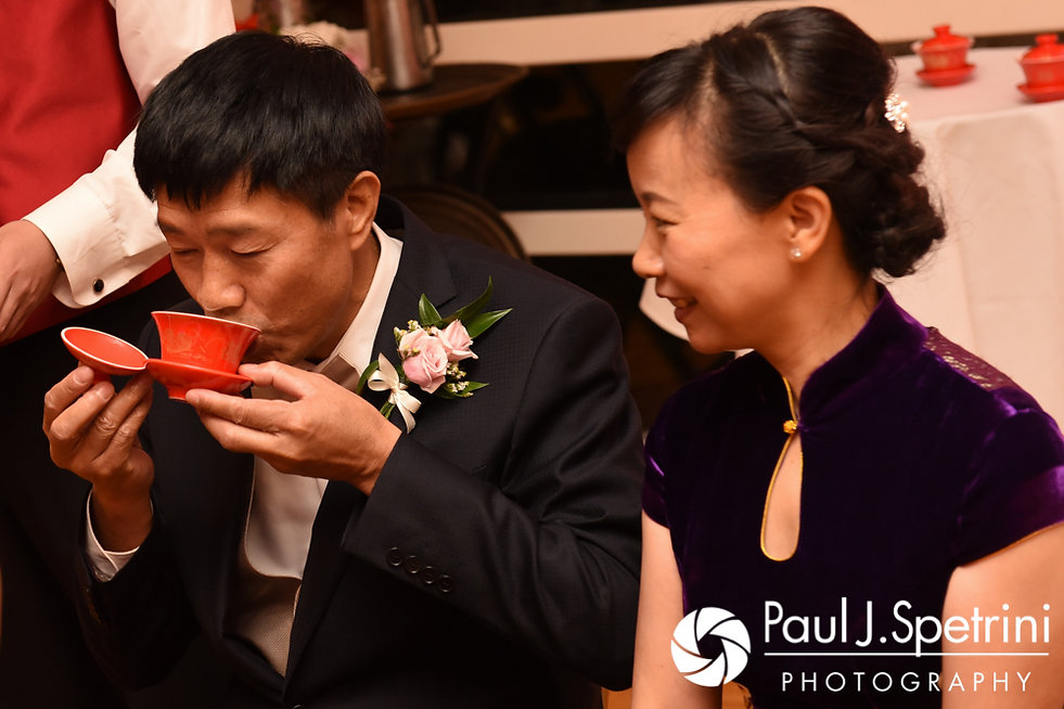 Cynthia and Ao's parents take part in a tea ceremony during Cynthia and Ao's August 2017 wedding reception at Lake Pearl in Wrentham, Massachusetts.