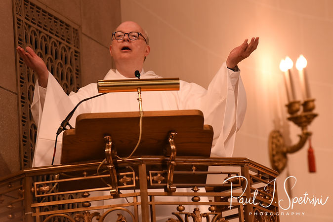 A priest gives a blessing during Brian & Sarah's June 2018 wedding ceremony at the College of the Holy Cross in Worcester, Massachusetts.
