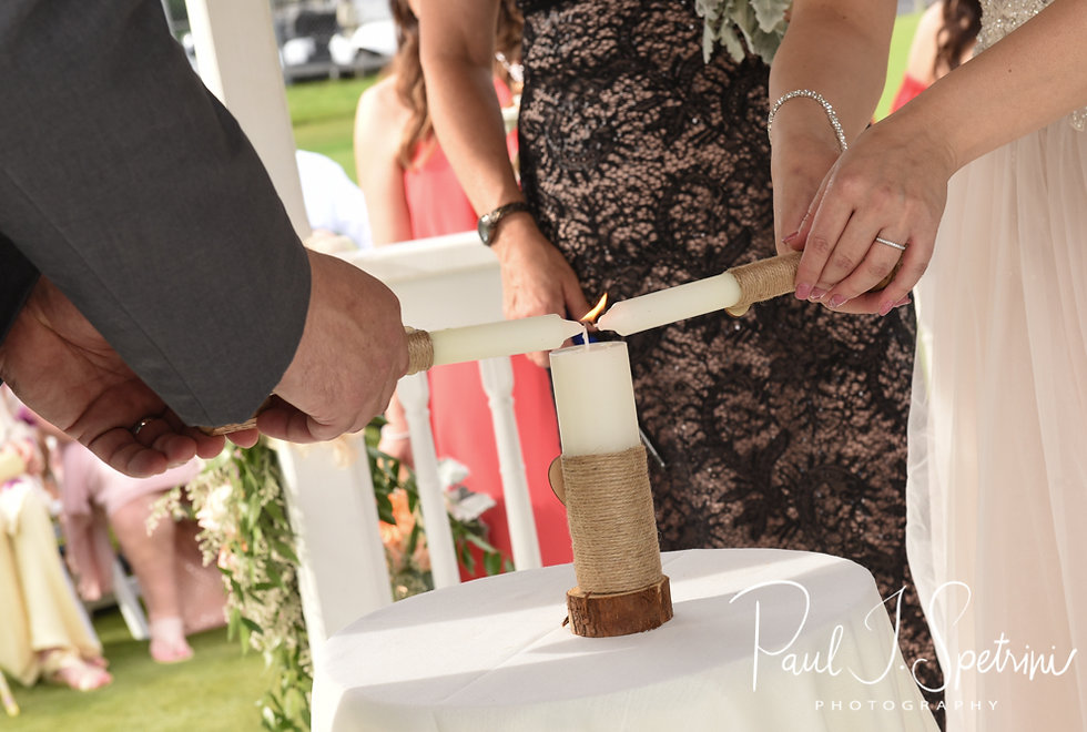 Stephanie and Jacob light a unity candle during their June 2018 wedding ceremony at Foster Country Club in Foster, Rhode Island.