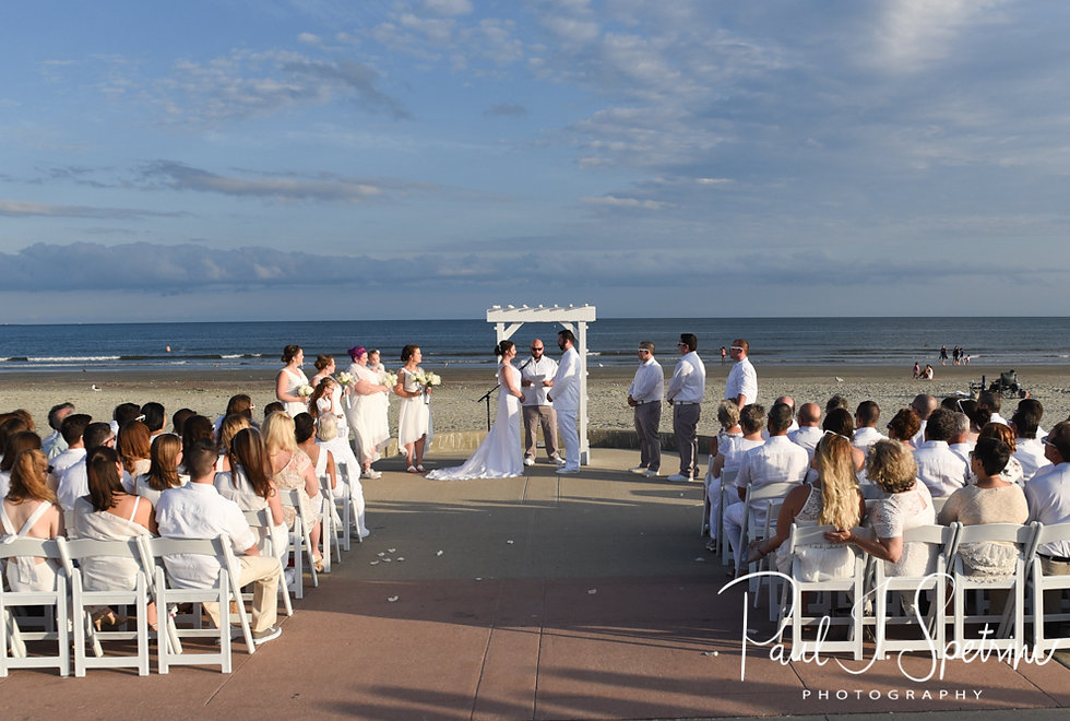Mike and Selah listen to their officiant during their August 2018 wedding ceremony at The Rotunda Ballroom at Easton's Beach in Newport, Rhode Island.