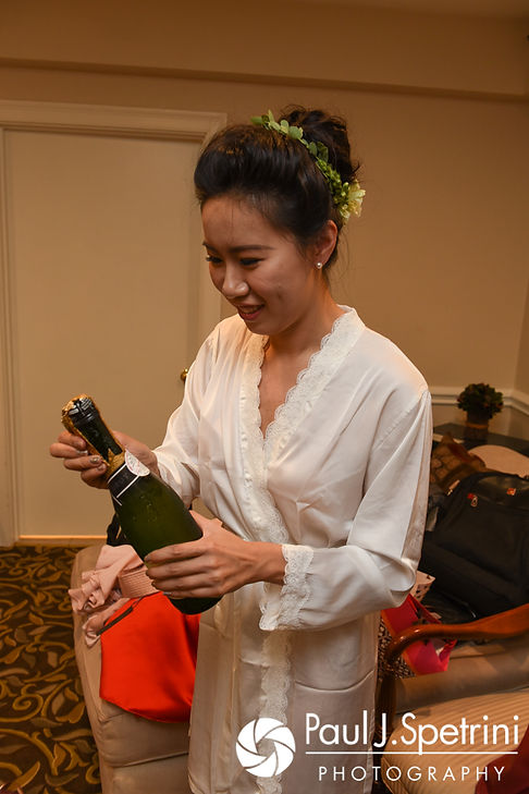 Cynthia opens a bottle of champagne prior to her August 2017 wedding ceremony at Lake Pearl in Wrentham, Massachusetts.