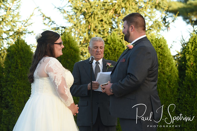 Katie and Steve listen to their officiant during their October 2018 wedding ceremony at The Villa at Ridder Country Club in East Bridgewater, Massachusetts.