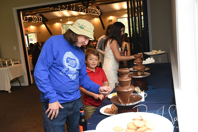 Josh gets dessert from a chocolate fountain during his October 2018 wedding reception at Loon Pond Lodge in Lakeville, Massachusetts.