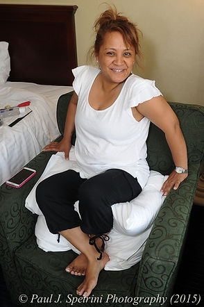 Jean Andrade sits on a pair of pillows to get her hair done.