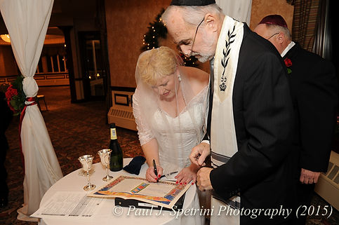 Cathy signs the ketubah at her and Ron's December 2015 wedding at Quidnessett Country Club in North Kingstown, Rhode Island.