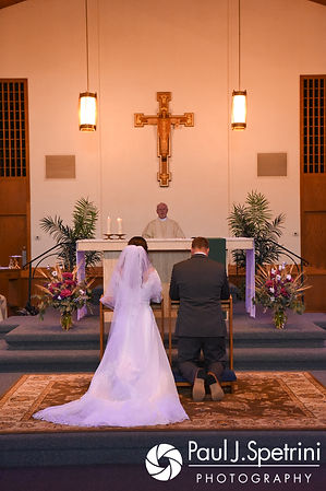 Samantha and Dale kneel during their October 2017 wedding ceremony at St. Robert's Church in Johnston, Rhode Island.