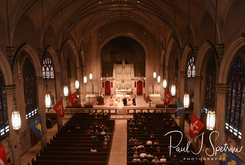 Courtney and Patrick listen to their priest speak during their September2018 wedding ceremony at St. Paul Church in Cranston, Rhode Island.