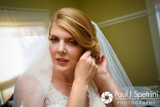 Rachel puts her earrings on prior to her October 2017 wedding ceremony at Castle Manor Inn in Gloucester, Massachusetts.