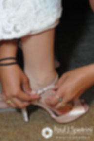Maria has help putting on her shoes prior to her March 2016 Rhode Island wedding.