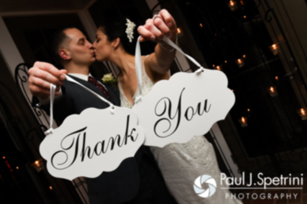 Gina and David hold up a Thank You sign during a photo from their December 2016 wedding reception at the Waterman Grille in Providence, Rhode Island.