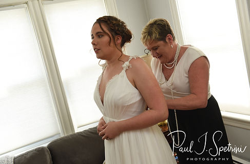 Ali's mother helps her put her dress on prior to her May 2018 wedding ceremony at the Roger Williams Park Botanical Center in Providence, Rhode Island.