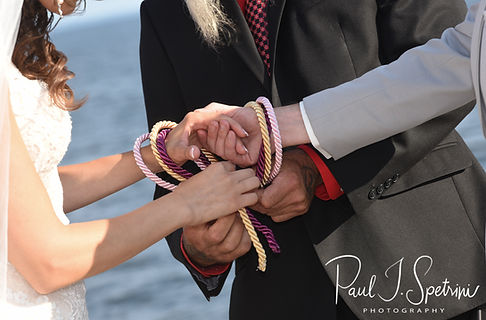 Beth and Bryan fasten their hands together during their August 2018 wedding ceremony at Fort Phoenix in Fairhaven, Massachusetts.