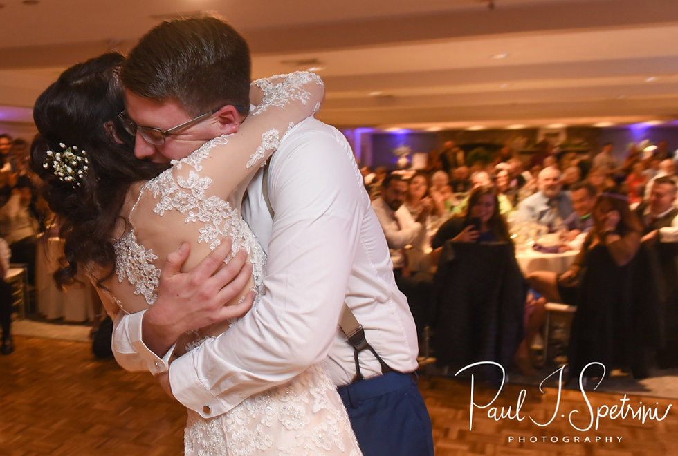 Stacey and Mack hug after a garter removal ceremony during their December 2018 wedding reception at Independence Harbor in Assonet, Massachusetts.