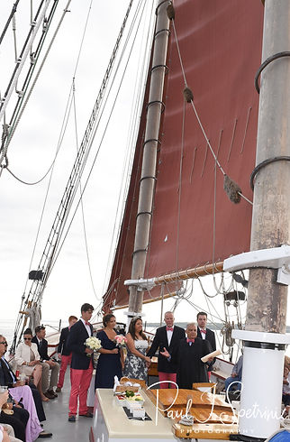 Mike and Kate listen to their officiant during their May 2018 wedding ceremony aboard the Schooner Aurora boat in the waters off Newport, Rhode Island.