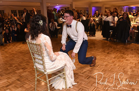Stacey and Mack participate in a garter removal ceremony during their December 2018 wedding reception at Independence Harbor in Assonet, Massachusetts.