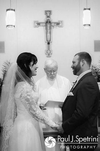 Samantha and Dale hold hands during their October 2017 wedding ceremony at St. Robert's Church in Johnston, Rhode Island.