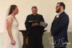 Rob and Allie listen to their officiant during their October 2018 wedding ceremony at South Ferry Church in Narragansett, Rhode Island.