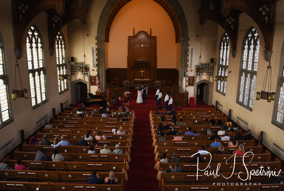 Courtnie and Richardson listen to their officiant speak during their August 2018 wedding ceremony at Glad Tidings Church in Quincy, Massachusetts.