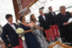 Mike and Kate smile during their May 2018 wedding ceremony aboard the Schooner Aurora boat in the waters off Newport, Rhode Island.