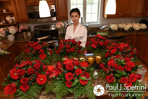 Cynthia poses for a photo near the flowers she put together prior to her August 2017 wedding ceremony at Lake Pearl in Wrentham, Massachusetts.