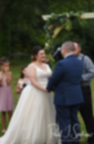 Adam and Ashley hold hands during their September2018 wedding ceremony at Stepping Stone Ranch in West Greenwich, Rhode Island.
