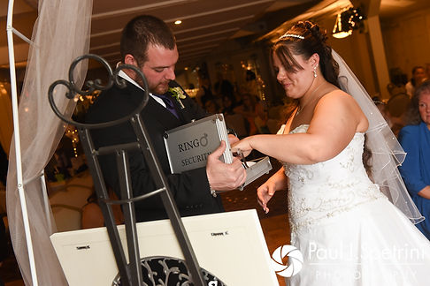 Clarissa and Jeffrey place a lock together on a piece of art during their June 2017 wedding ceremony at Twelve Acres in Smithfield, Rhode Island.