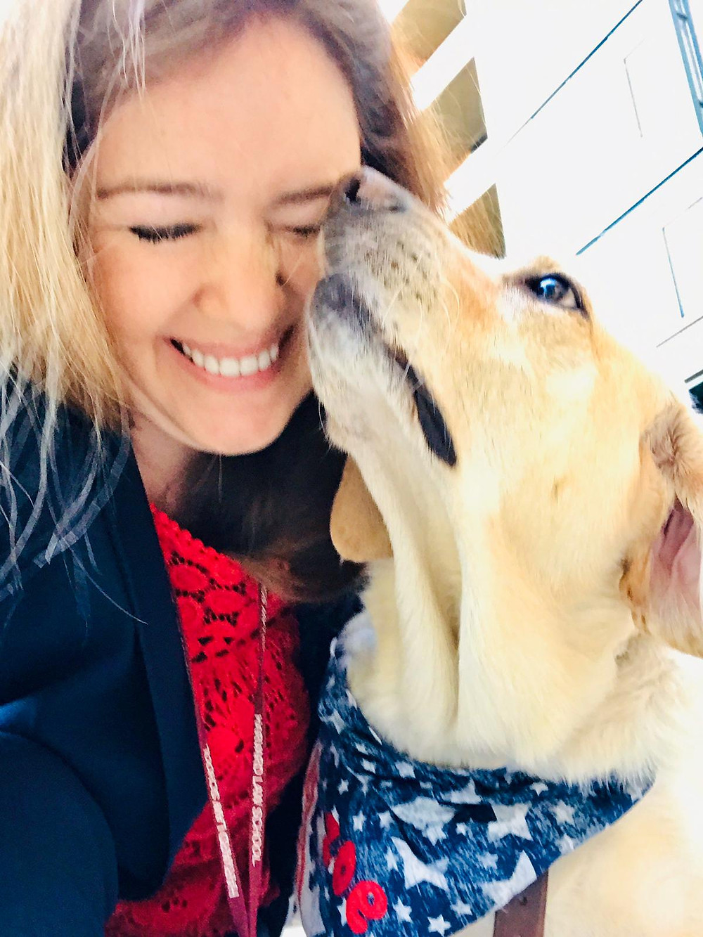 PD: Kristin is smiling and laughing as Zoe nudges her nose up to Kristin's face. Zoe is wearing a festive blue bandana with white stars, and ZOE in red letters.