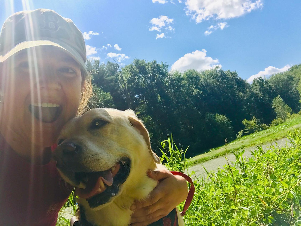 PD: Zoe and Kristin on a hike in a park. Kristin has her arm around Zoe and they both have huge smiles on their faces. There is a green wetland in the background and the sky is blue and sunlight is shining bright and there is a stream of light coming straight down onto Kristin's head.
